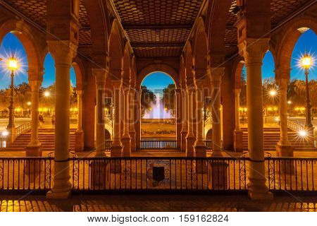 Beautiful Gallery with columns on Spain Square or Plaza de Espana in Seville at night, Andalusia, Spain