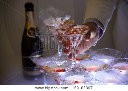 Gentleman takes a glass of champagne at the party. Luxury festive evening with alcohol. Champagne with bubbles. The festive drink of the elite.
