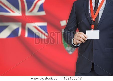 Businessman Holding Badge On A Lanyard With Canadian Province Flag On Background - Manitoba