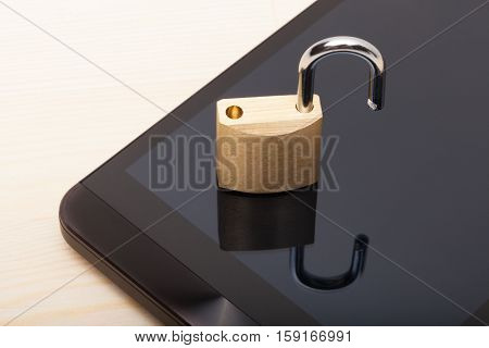 Small Unlocked Lock Over A Smartphone. Mobile Phone Security And Data Protection Concept