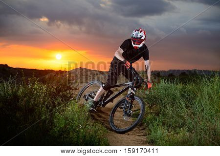 Professional Cyclist Riding the Bike on the Mountain Rocky Trail at Sunset. Extreme Sports