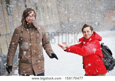 Two interesting young men walking in the street during a winter snowfall laugh and have fun.