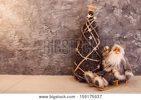 Small Santa toy sitting on a wooden sled near wicker Christmas tree at the gray concrete wall background. Copy space at left. Horizontal.