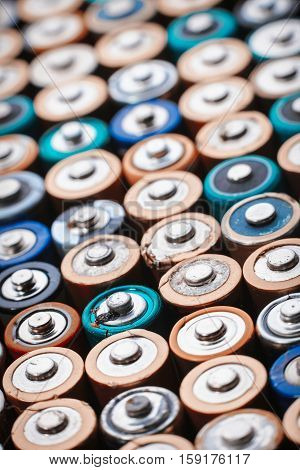 Close up top view on rows of selection of AA batteries energy abstract background of colorful batteries. Alkaline battery aa size. Several batteries are next to each other. Many aa batteries.