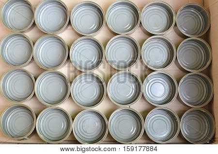 empty tin food can in brown paper box