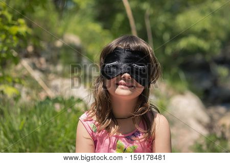 funny smiling little girl with sleeping mask on her eyes in outdoor park on summer day