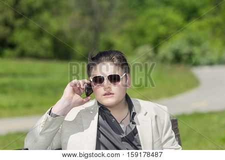 young handsome adolescent boy sitting summer outdoor park and talking on the phone