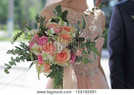 Bride holding a beautiful bridal bouquet. Wedding bouquet of peach roses  single-head pink rose aqua eucalyptus ruscus gypsophila