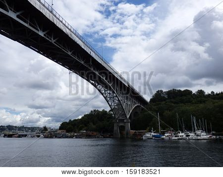Aurora Bridge under repair towers over Union Lake with boats lining the shore in Seattle Washington.