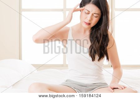 Beautiful Asian Woman Suffering Headache And Massage Forehead