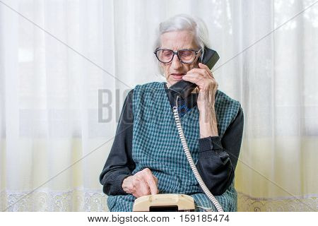 Elderly Woman Using The Phone Indoors