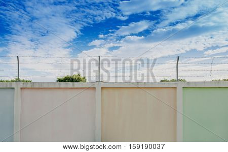 concrete fence with barbed wire and sky background.