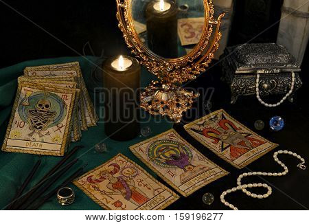 Esoteric still life with the Tarot cards, candle, mirror and crystals. Halloween concept, black magic ritual or spell with occult and mystic symbols, divination rite. Vintage objects on table