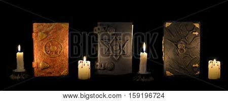 Three black magic book with burning candles in the darkness. Esoteric and occult objects on witch, divination ritual or Halloween concept. Mystic background