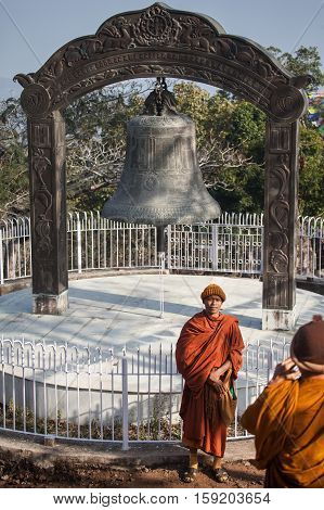 Monks - pilgrims are photographed against the background of the big bell established on Rajgir hills on lands of the capital of the ancient empire of Magadha near the place where Buddha on Vulture Peak (Griddhakuta Hill) has made the second and third turn
