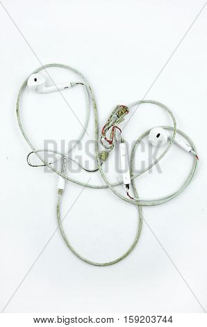Old torn white headphones. On a white background.