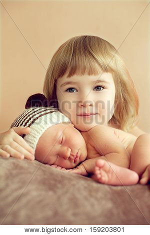 Little girl hugging her newborn sleeping brother. Good morning in a happy family. For the love of children to their brothers and sisters