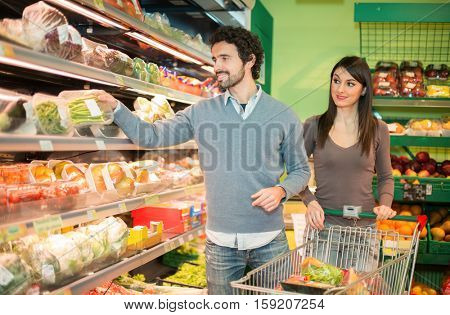Couple choosing the best food in a grocery store