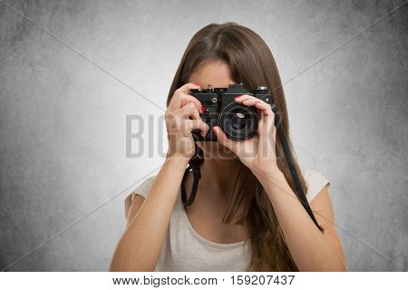 Portrait of a female photographer using an old camera