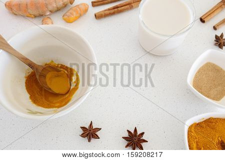 turmeric almond mink cinnamon ginger and honeyingredients for making Turmeric latte Golden milk Turmeric milk healthy hipster drink