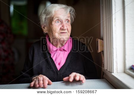 Elderly woman surprised stares out of the window.