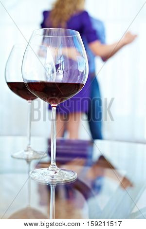 Close-up of wineglasses on the background of dancing people