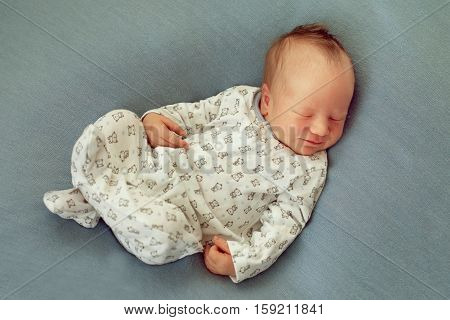 Newborn baby boy asleep on a blue background in white pajamas with prints and smiling in her sleep. A happy childhood