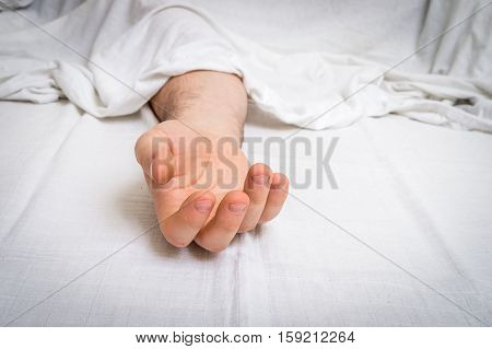 The Dead Man's Body Under White Cloth With Focus On Hand