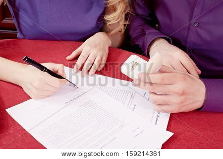 Close-up of woman signing a prenuptial agreement and man sitting near her with engagement ring