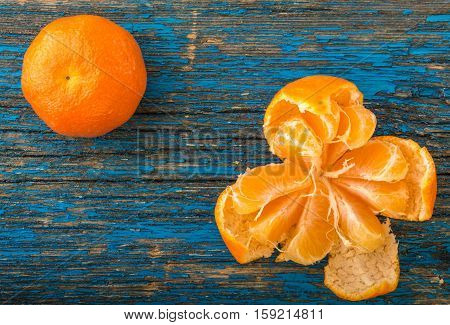 mandarines, peeled tangerine and tangerine slices on a blue wooden table top view