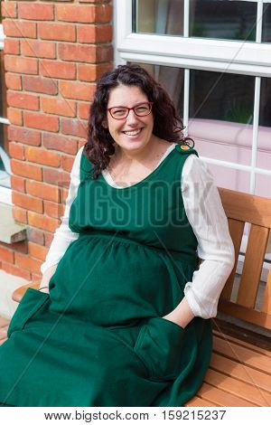 Pregnant Woman In A Green Dress Sitting In Front Of Her House