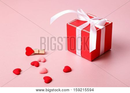 Valentine day composition: red gift box with bow spring flowers clamp and small hearts on light pink background.