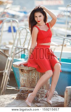 Young beautiful brunette woman with thick long hair and brown eyes,a beautiful figure,light makeup and red lipstick,wears large gold earrings,dressed in a summer skirt and vest red,posing in the summer near the sea on a pier near yachts and boats