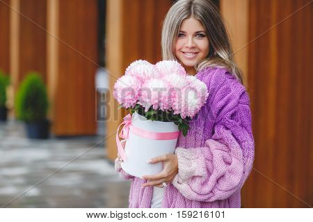 Young beautiful woman with long straight blond hair and gray eyes, dressed in a pink-and-purple-white, a beautiful knitted coat, light make-up and glamorous smile in the hands holding a large bouquet of pink flowers, autumnal portrait on a street.