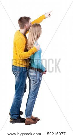 young couple pointing at wal Back view. Rear view people collection.  Isolated over white background. guy in the yellow sweater hugging behind her and shows her something interesting in sky