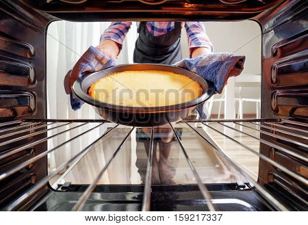 Housewife Using Dishcloth For Taking Cheesecake Out Of Oven