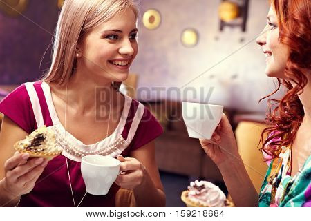 Two female friends talking and eating dessert