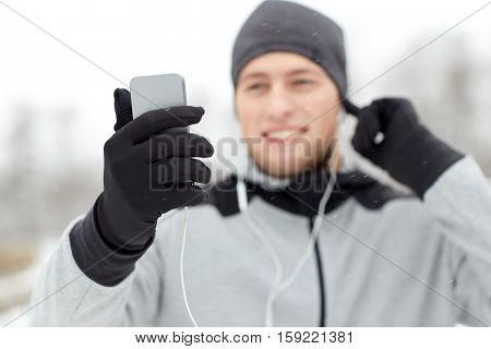 fitness, sport, people, technology and healthy lifestyle concept - close up of happy smiling young man in earphones with smartphone listening to music in winter