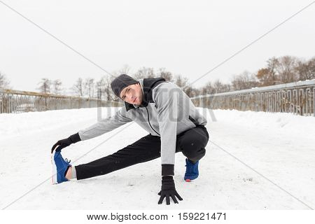 fitness, sport, people, exercising and healthy lifestyle concept - young man stretching leg and warmig up on snow covered winter bridge