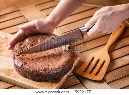Hand Holding Knife And Cutting Freshly Baked Brownie Cake