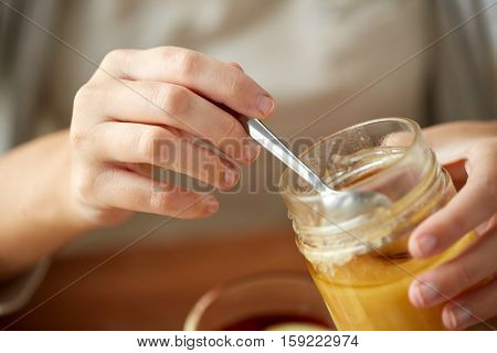 health, traditional medicine and ethnoscience concept - close up of woman hands with honey jar and spoon