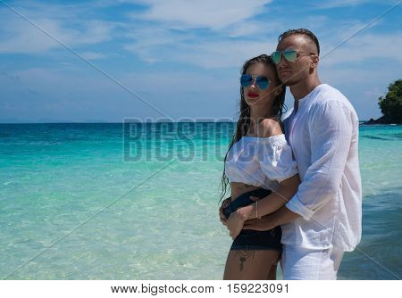 Sensual pretty couple wearing white clothes and sunglasses embracing on the beach and looking at the view over beautiful lagoon sea and sky background