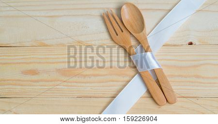 Wooden Kitchenwares spoon and fork wrapped by white ribbon on wooden