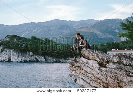 Happy Man And Women Sit Down On A Rock Mountain In Montenegro, Freedom And Travel Cocept