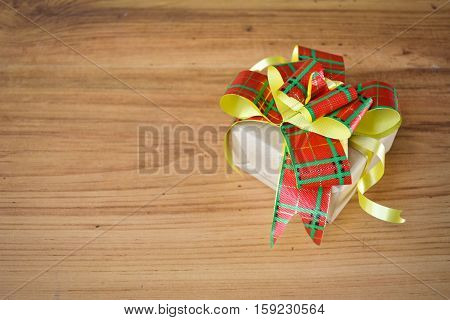 Little beautiful gift box on wood background vintage tone and soft focus concept of chritmas and new year day