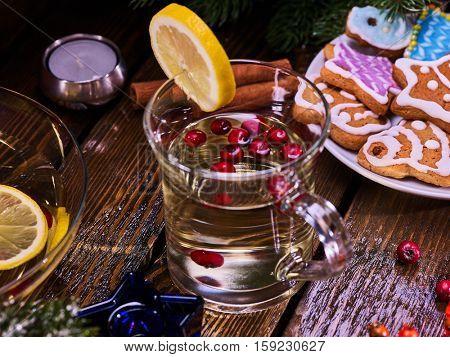 Top view of christmas glass latte mug and Christmas multicolored cookies on plate. Mag decoration lemon slice on wooden table and cinnamon sticks.