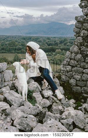 Young Woman Wearing Beige Sweater, Hat And Jeans With White Dog Posing Against Stone Wall, Swag Stre