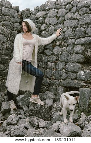 Trendy Hipster Woman Wearing Beige Sweater, Hat And Jeans Posing Against Stone Wall, Swag Street Sty