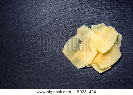 Top View Of Tasty Fresh Yellow Thin Slice Parm Cheese On Black Stone Slate Background, Close Up