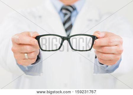 doctor optician glasses optometrist optical store new vision men shop closeup occupation medical medicine eyeglasses lens human hand caucasian concept - stock image